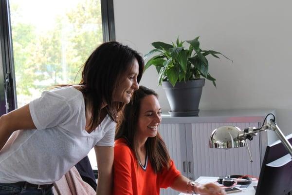 Deux collaboratrices d'Avanci souriant devant un écran