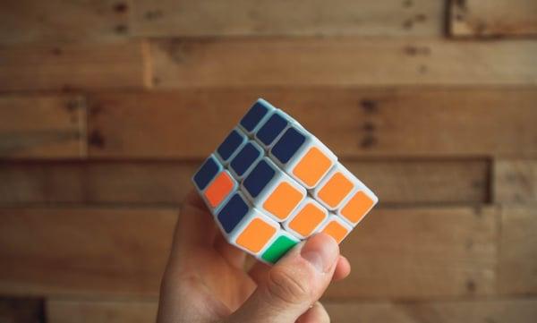 Gros plan d'un Rubik's Cube tenu dans une main