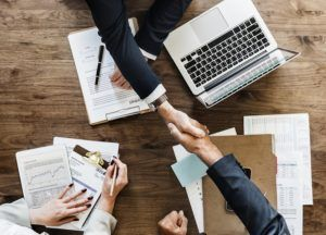 Deux hommes se serrant la main au dessus d'un bureau