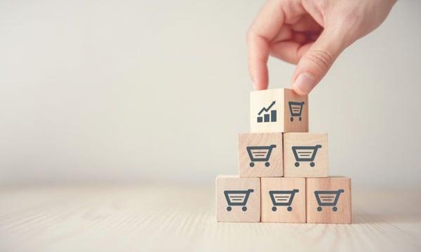 Cubes avec un dessin de caddie, métaphore des ventes