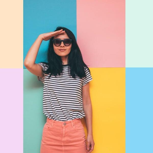 Personne avec jupe saumon, haut rayé, cheveux longs et lunettes de soleil devant un mur coloré